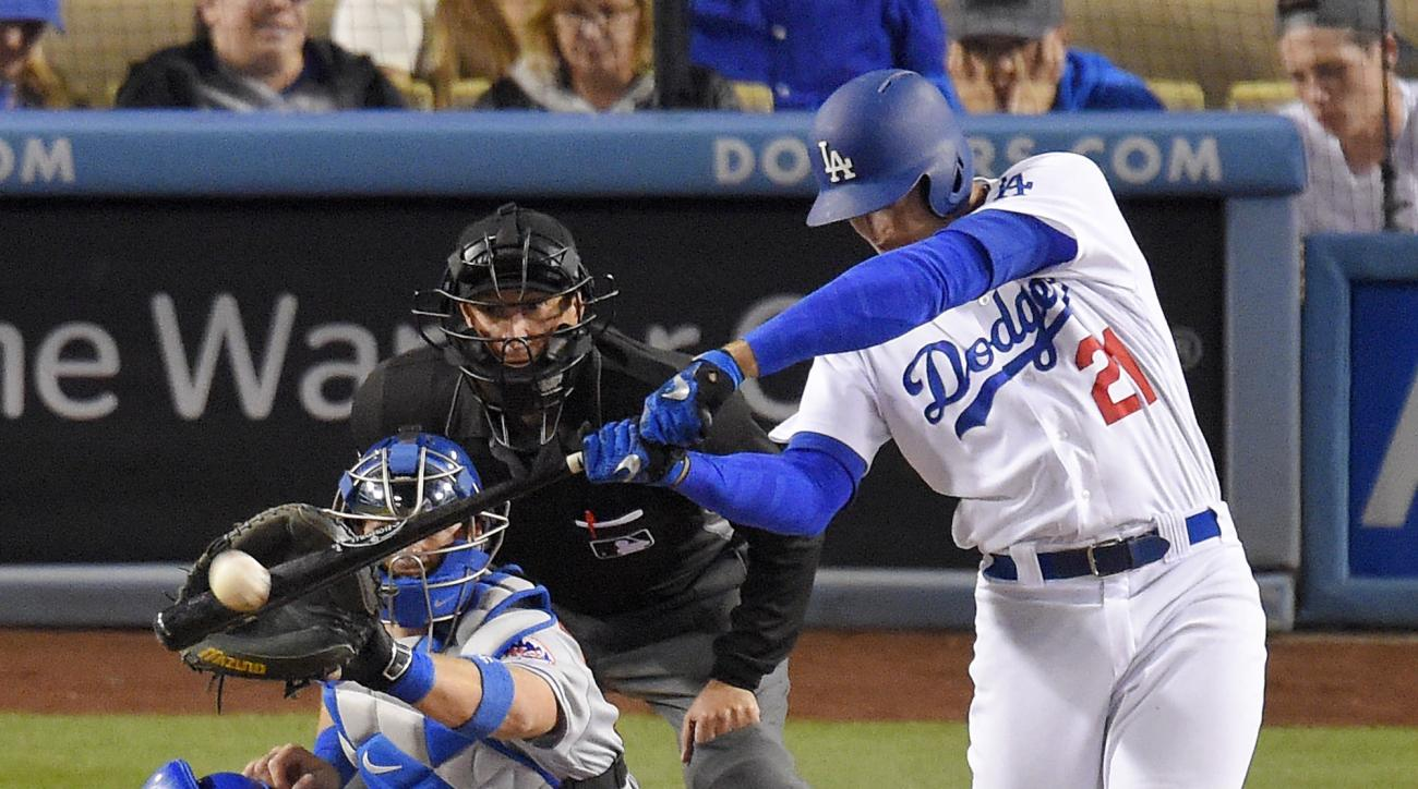 Los Angeles Dodgers' Trayce Thompson, right, hits a two-run home run as New York Mets catcher Kevin Plawecki, left, watches along with home plate umpire Jim Reynolds during the fourth inning of a baseball game, Monday, May 9, 2016, in Los Angeles. (AP Pho