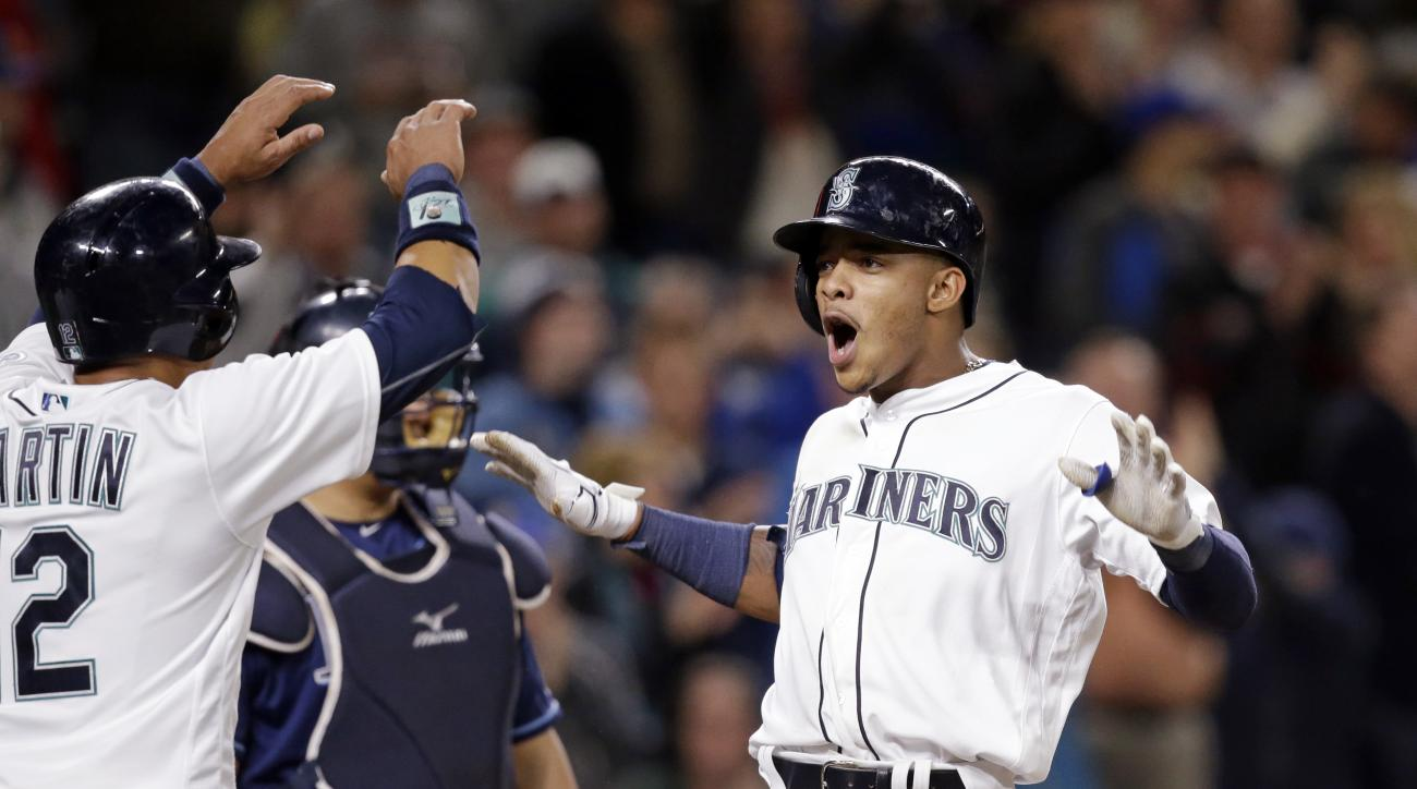 Seattle Mariners' Ketel Marte, right, is greeted by Leonys Martin as Marte crosses home on his three-run home run and Tampa Bay Rays catcher Hank Conger looks on in the sixth inning of a baseball game Monday, May 9, 2016, in Seattle. (AP Photo/Elaine Thom