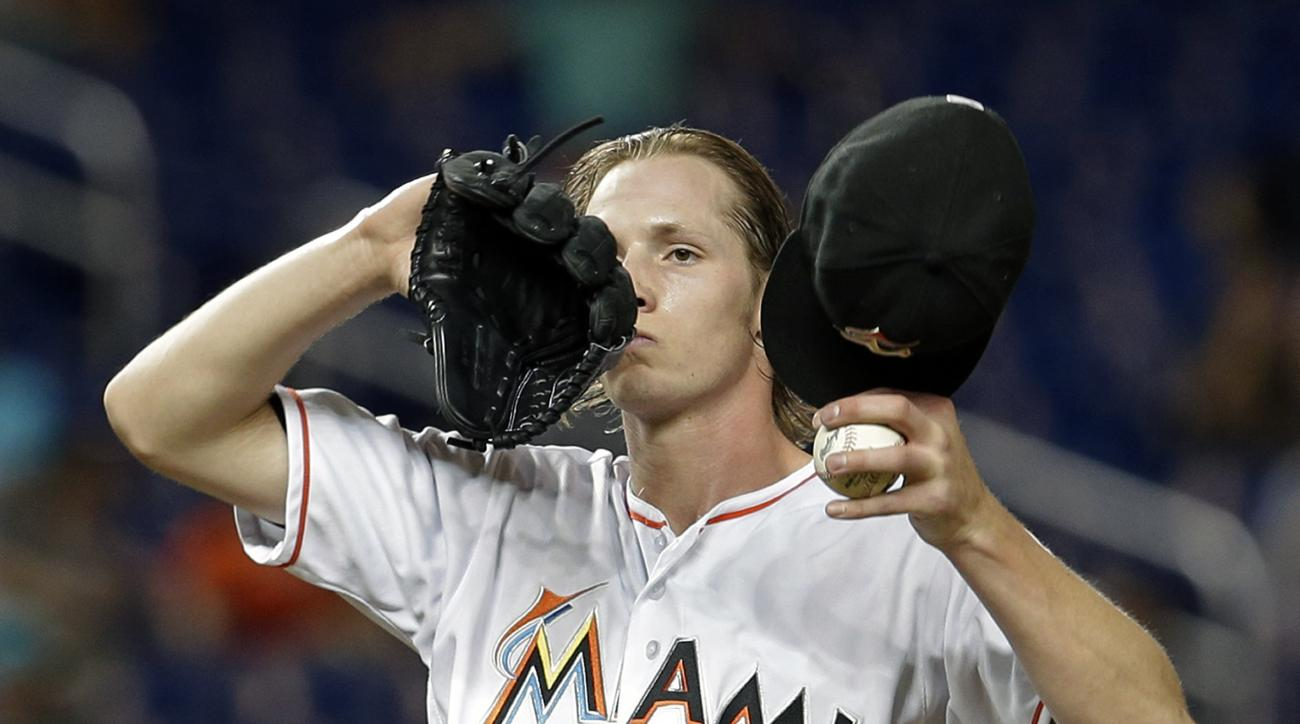 Miami Marlins starting pitcher Adam Conley (61) wipes his face after walking Milwaukee Brewers' Ryan Braun in the fourth inning of a baseball game, Tuesday, May 10, 2016, in Miami. (AP Photo/Alan Diaz)