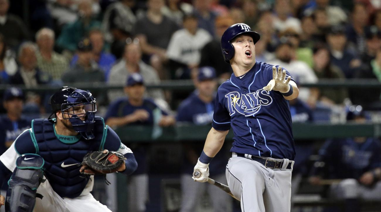 Tampa Bay Rays' Corey Dickerson spins around as he strikes out swinging during the seventh inning of a baseball game as Seattle Mariners catcher Chris Iannetta watches, Tuesday, May 10, 2016, in Seattle. (AP Photo/Elaine Thompson)