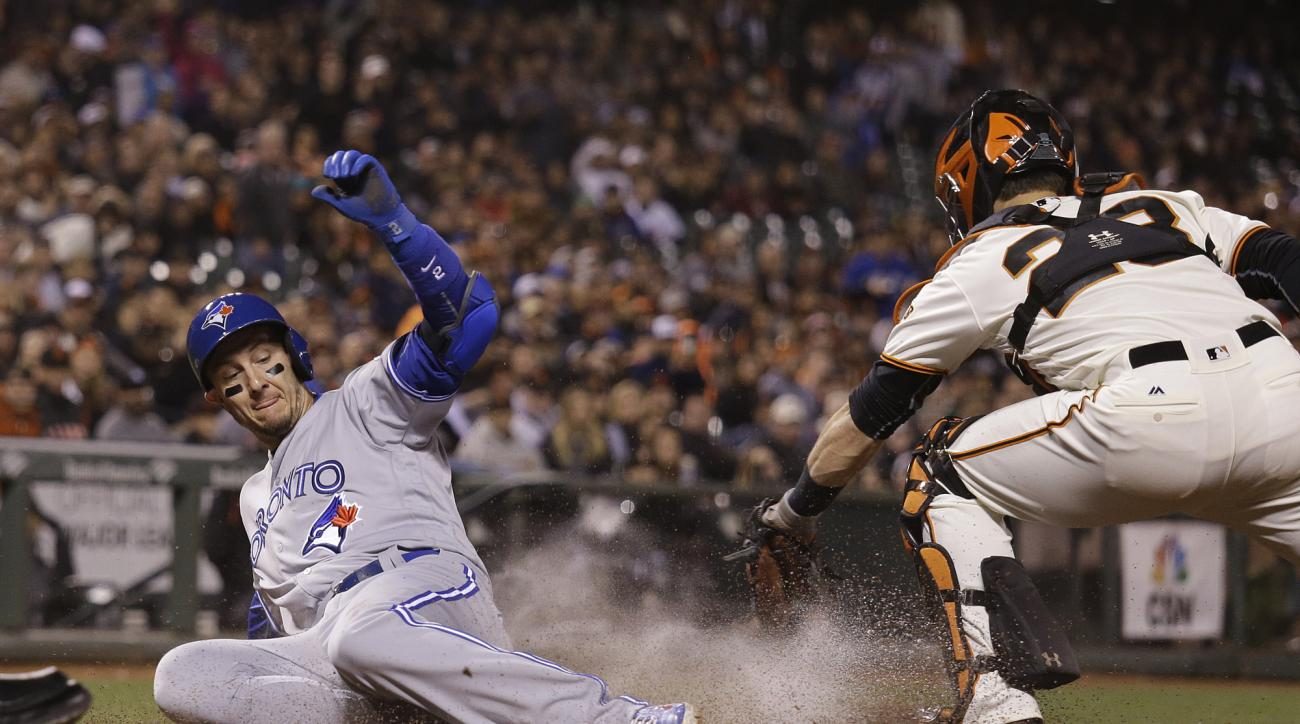 Toronto Blue Jays' Troy Tulowitzki slides safely into home plate to score against San Francisco Giants catcher Buster Posey during the ninth inning of a baseball game Tuesday, May 10, 2016, in San Francisco. (AP Photo/Eric Risberg)