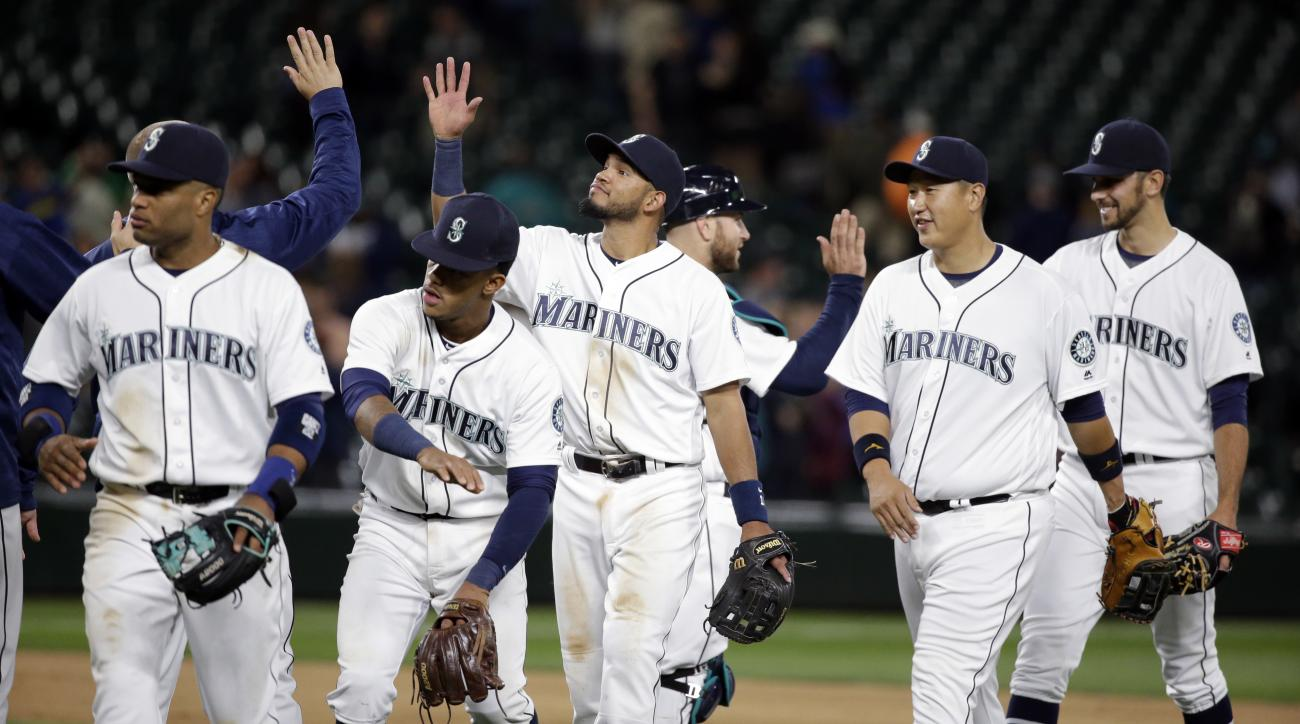 Seattle Mariners players share congratulations after the Mariners defeated the Tampa Bay Rays 6-4 in a baseball game Tuesday, May 10, 2016, in Seattle. (AP Photo/Elaine Thompson)