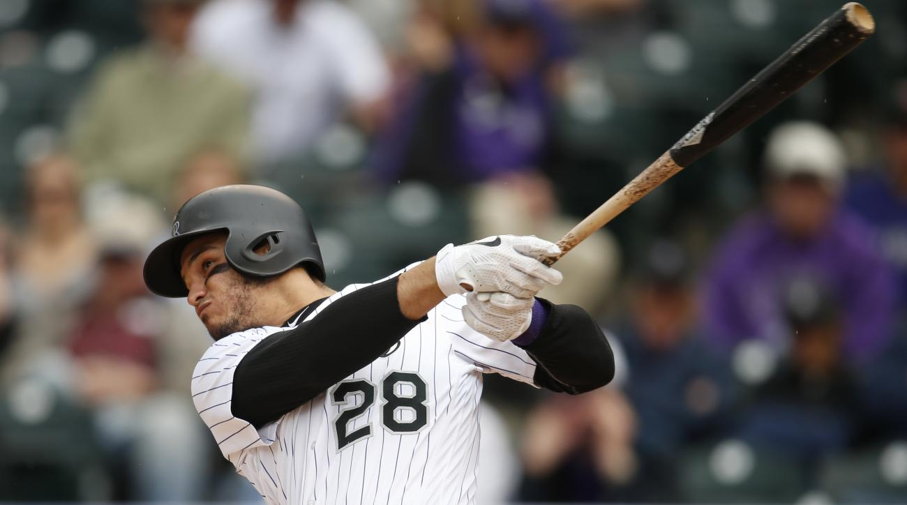 Colorado Rockies' Nolan Arenado follows through with his swing after connecting for a solo home run off Arizona Diamondbacks relief pitcher Tyler Clippard in the eighth inning of a baseball game Wednesday, May 11, 2016, in Denver. The Rockies won 8-7. (AP