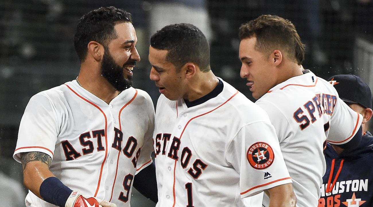 Houston Astros' Marwin Gonzalez (9) celebrates his game-winning two-run home run with Carlos Correa (1) and George Springer, right, in the 16th inning of a baseball game against the Cleveland Indians, Wednesday, May 11, 2016, in Houston. Houston won 5-3.