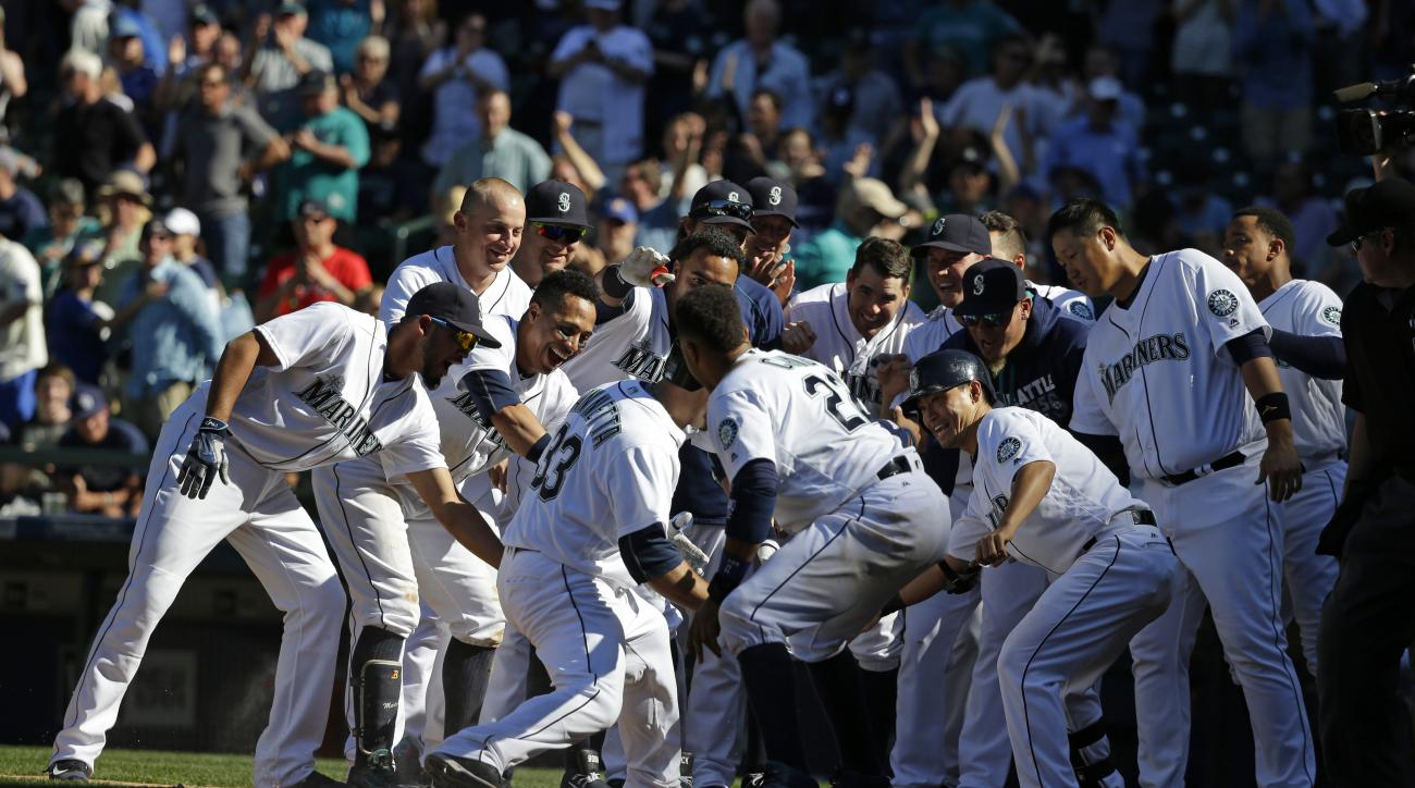 Seattle Mariners' Chris Iannetta (33) is greeted by teammates at home plate after he hit a walk-off solo home run in the 11th inning of a baseball game against the Tampa Bay Rays, Wednesday, May 11, 2016, in Seattle. The Mariners beat the Rays 6-5. (AP Ph