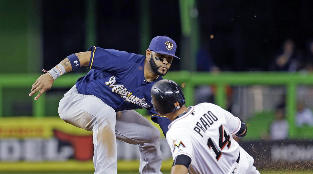 Milwaukee Brewers shortstop Jonathan Villar tags out Miami Marlins' Martin Prado (14) trying to steal second base during the first inning of a baseball game Wednesday, May 11, 2016, in Miami. (AP Photo/Alan Diaz)