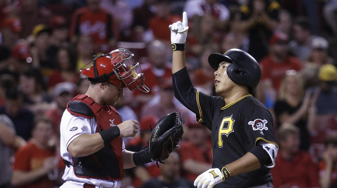Pittsburgh Pirates' Jung Ho Kang, right, passes Cincinnati Reds catcher Tucker Barnhart as he celebrates after hitting a solo home run during the seventh inning of a baseball game, Wednesday, May 11, 2016, in Cincinnati. (AP Photo/John Minchillo)