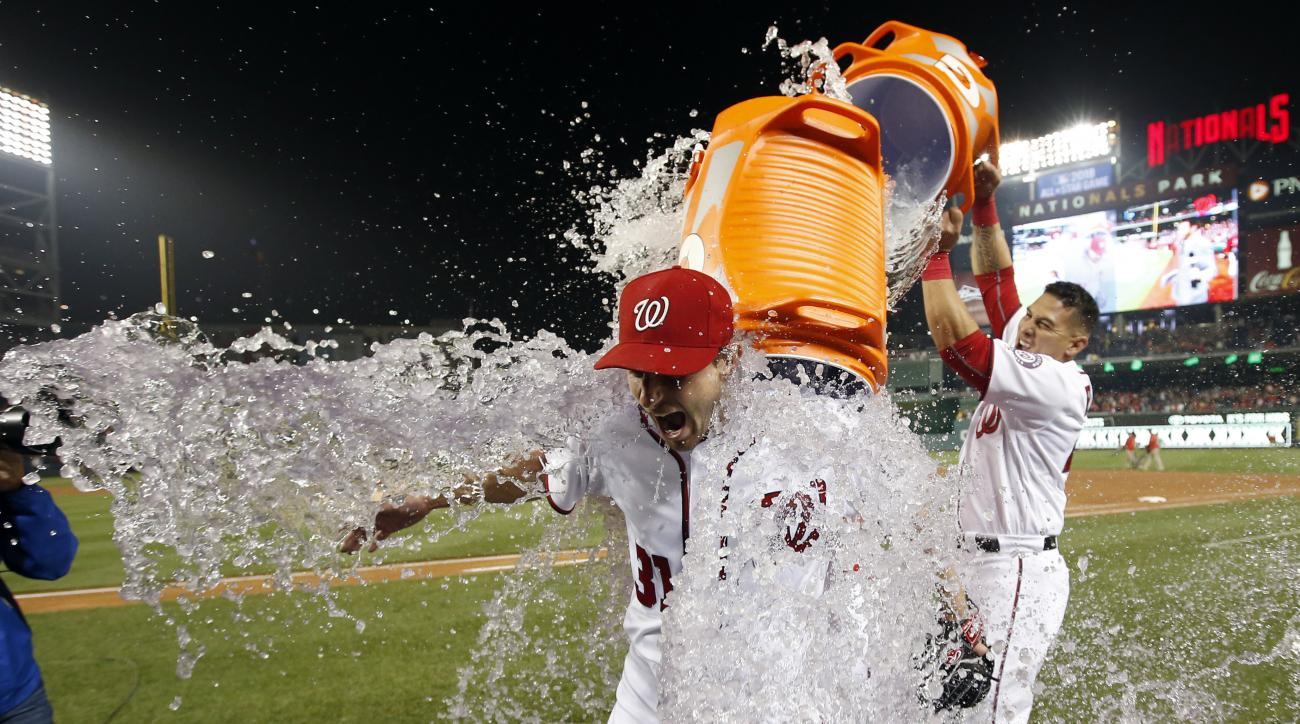 Washington Nationals starting pitcher Max Scherzer is doused by catcher Wilson Ramos after the Nationals defeated the Detroit Tigers in a baseball game at Nationals Park, Wednesday, May 11, 2016, in Washington. Scherzer struck out 20 batters, tying the ma