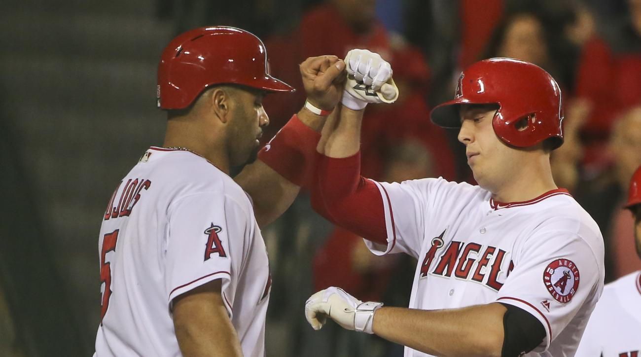 Los Angeles Angels' C.J. Cron is congratulated by Albert Pujols, left, at home plate after hitting a two-run home run against the St. Louis Cardinals during the fourth inning of a baseball game Wednesday, May 11, 2016, in Anaheim, Calif. (AP Photo/Lenny I