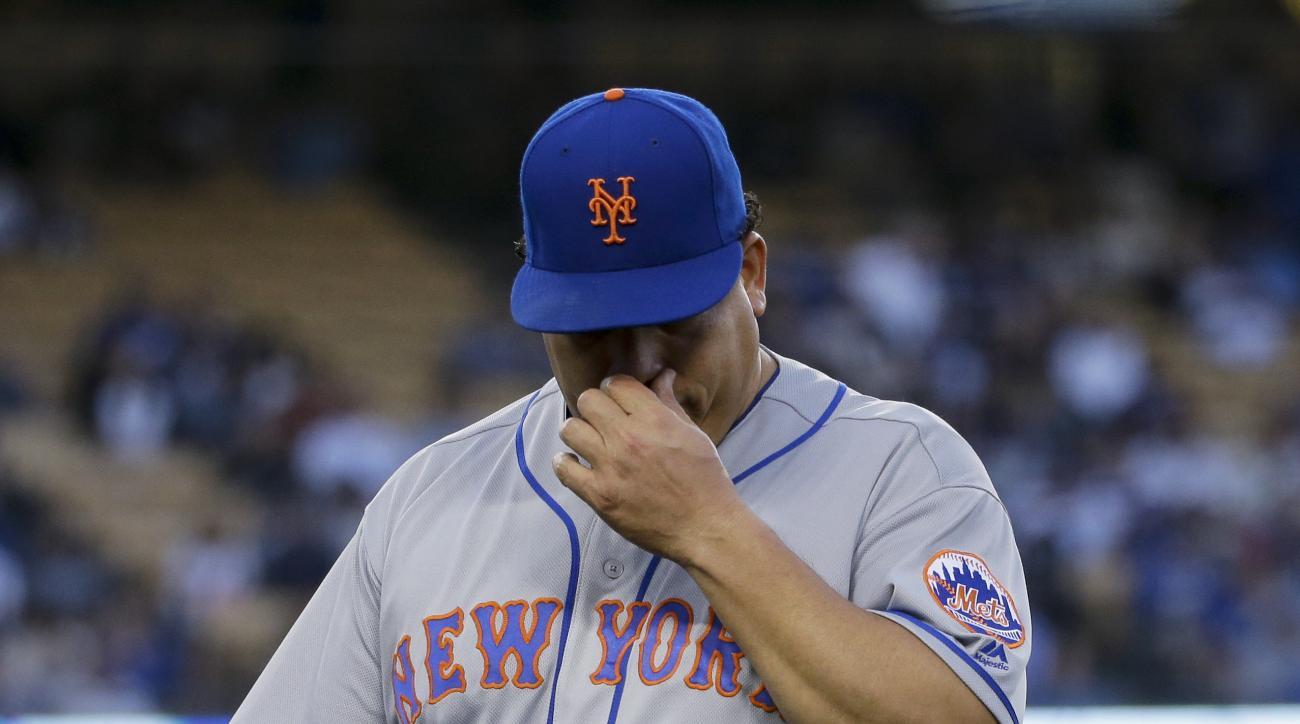 New York Mets starting pitcher Bartolo Colon wipes his face as he walks off the field after giving up four runs to the Los Angeles Dodgers in the first inning of a baseball game in Los Angeles, Thursday, May 12, 2016. (AP Photo/Chris Carlson)