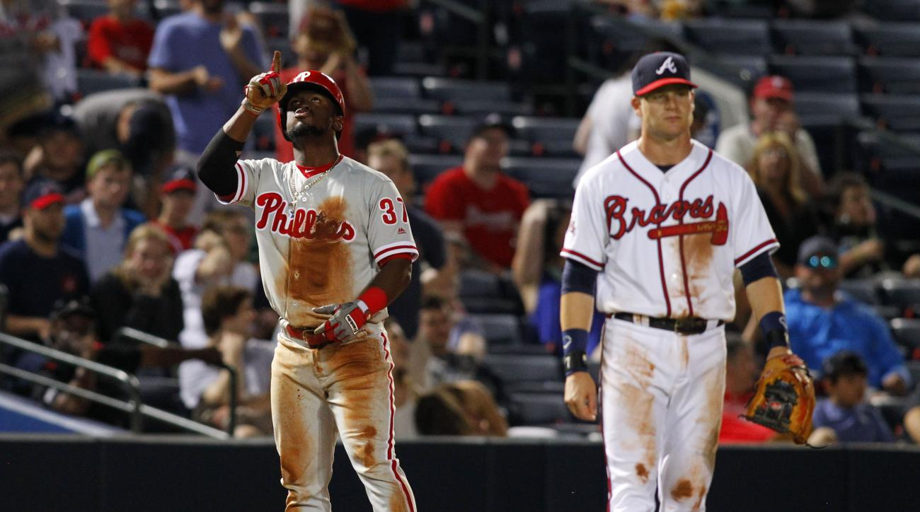 Philadelphia Phillies center fielder Odubel Herrera (37) celebrates a triple as Atlanta Braves' Gordon Beckham walks to the mound in the tenth inning of a baseball game against the Atlanta Braves, Thursday, May 12, 2016, in Atlanta. The Phillies won 7-4.