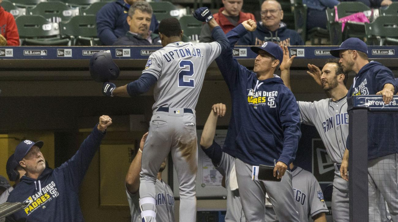 San Diego Padres' Melvin Upton Jr. is greeted at the dugout by teammates after hitting a solo home run off of Milwaukee Brewers' Tyler Thornburg during the ninth inning of a baseball game Thursday, May 12, 2016, in Milwaukee. (AP Photo/Tom Lynn)