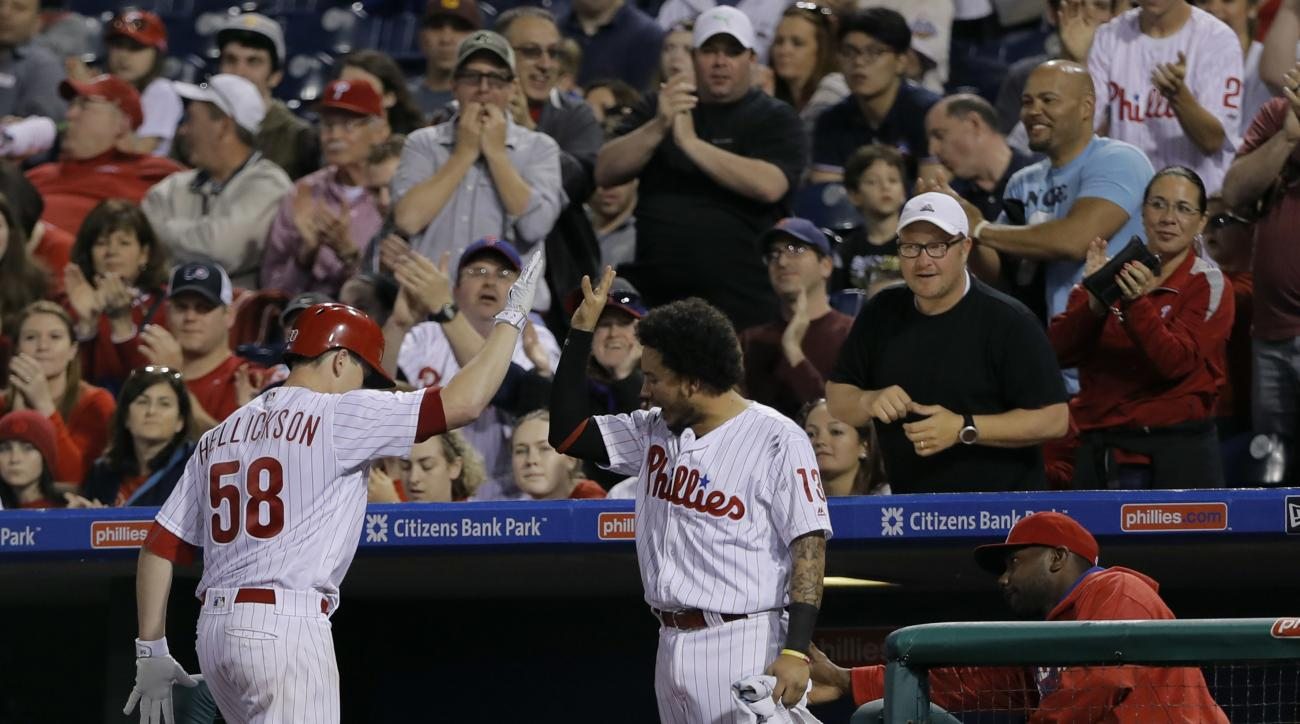 Philadelphia Phillies' Jeremy Hellickson, left, and Freddy Galvis celebrate after Hellickson's run-scoring sacrifice bunt off Cincinnati Reds starting pitcher Brandon Finnegan during the fourth inning of a baseball game, Friday, May 13, 2016, in Philadelp