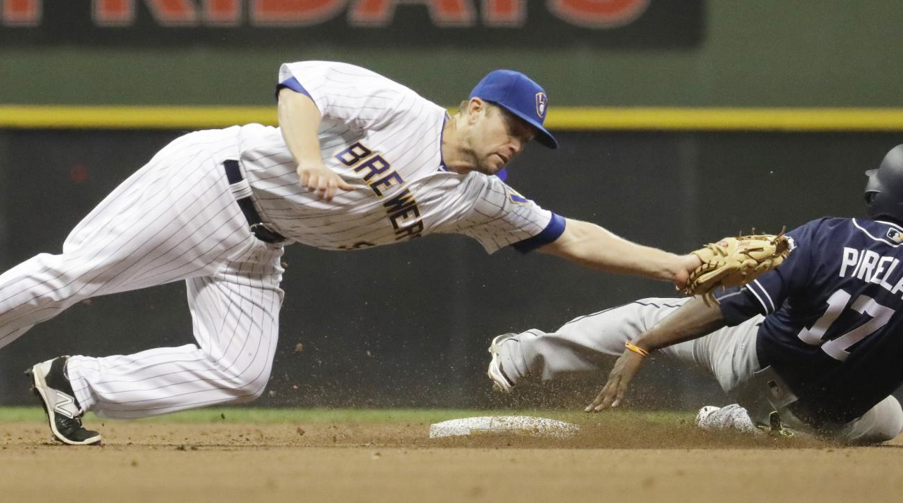 Milwaukee Brewers' Aaron Hill tags out San Diego Padres' Jose Pirela as he is caught stealing second during the seventh inning of a baseball game Friday, May 13, 2016, in Milwaukee. (AP Photo/Morry Gash)