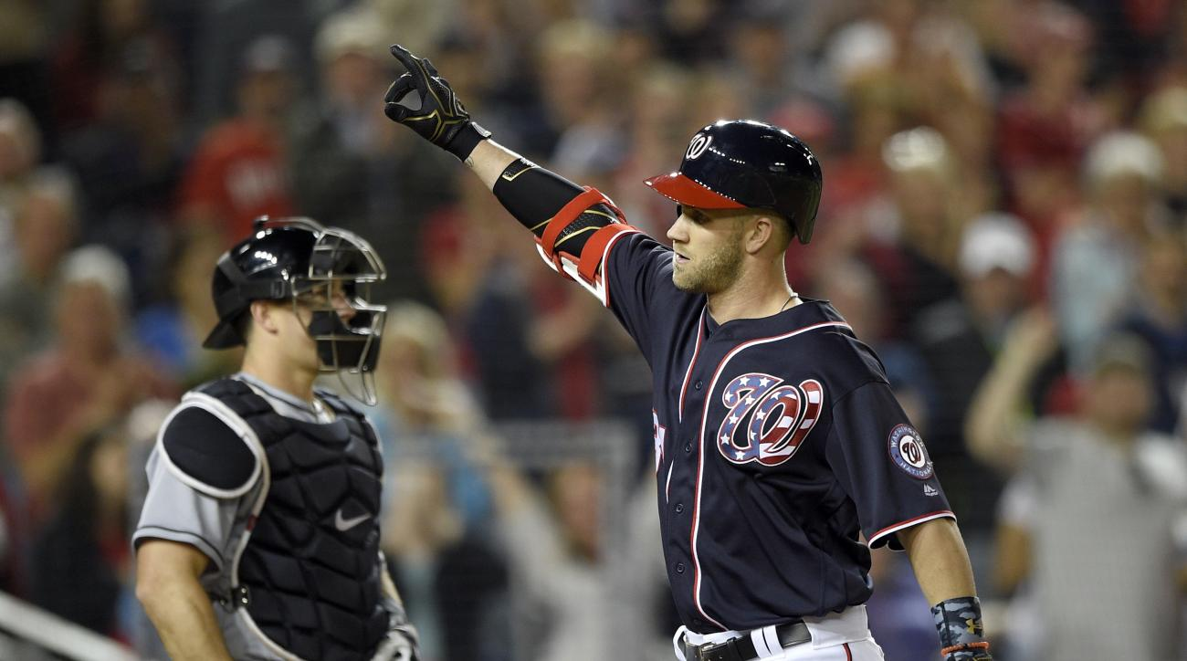 Washington Nationals' Bryce Harper, right, celebrates his two-run home run during the seventh inning of a baseball game as Miami Marlins catcher J.T. Realmuto looks on at left, Friday, May 13, 2016, in Washington. (AP Photo/Nick Wass)