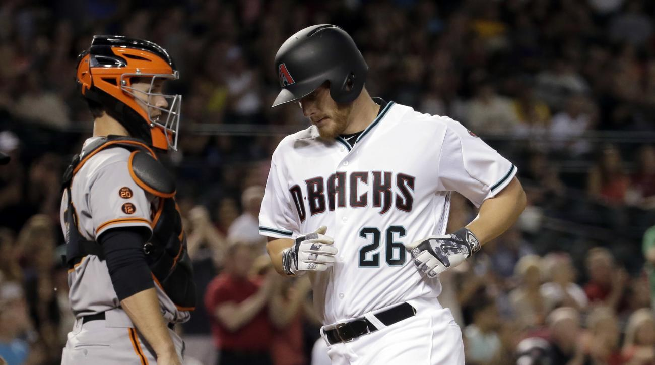 Arizona Diamondbacks' Shelby Miller (26) scores on a base hit by teammate Jean Segura during the fifth inning of a baseball game as San Francisco Giants' Buster Posey looks away Friday, May 13, 2016, in Phoenix. (AP Photo/Matt York)