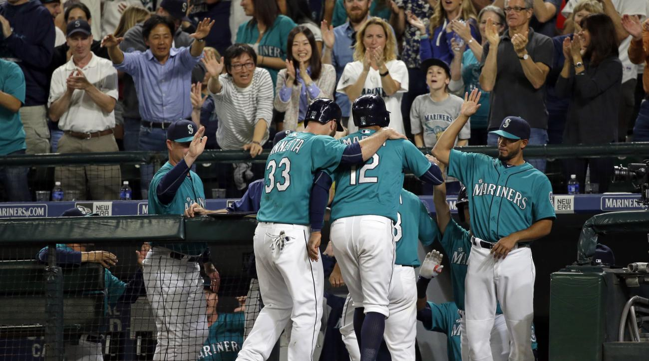 Fans cheer as Seattle Mariners' Chris Iannetta (33) and Leonys Martin (12) are greeted at the dugout by Luis Sardinas, right, after Iannetta and Martin scored on a three-run triple by Ketel Marte during the sixth inning of a baseball game against the Los