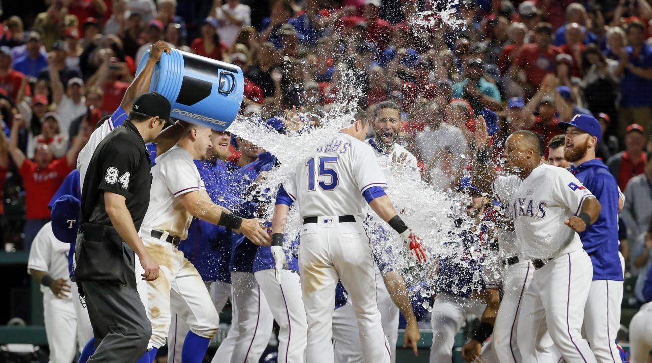 Texas Rangers' Drew Stubbs (15) is showered and greeted by teammates as he crosses home plate on a walkoff solo home run off Toronto Blue Jays relief pitcher Gavin Floyd in the 10th inning of a baseball game, Saturday, May 14, 2016, in Arlington, Texas. (