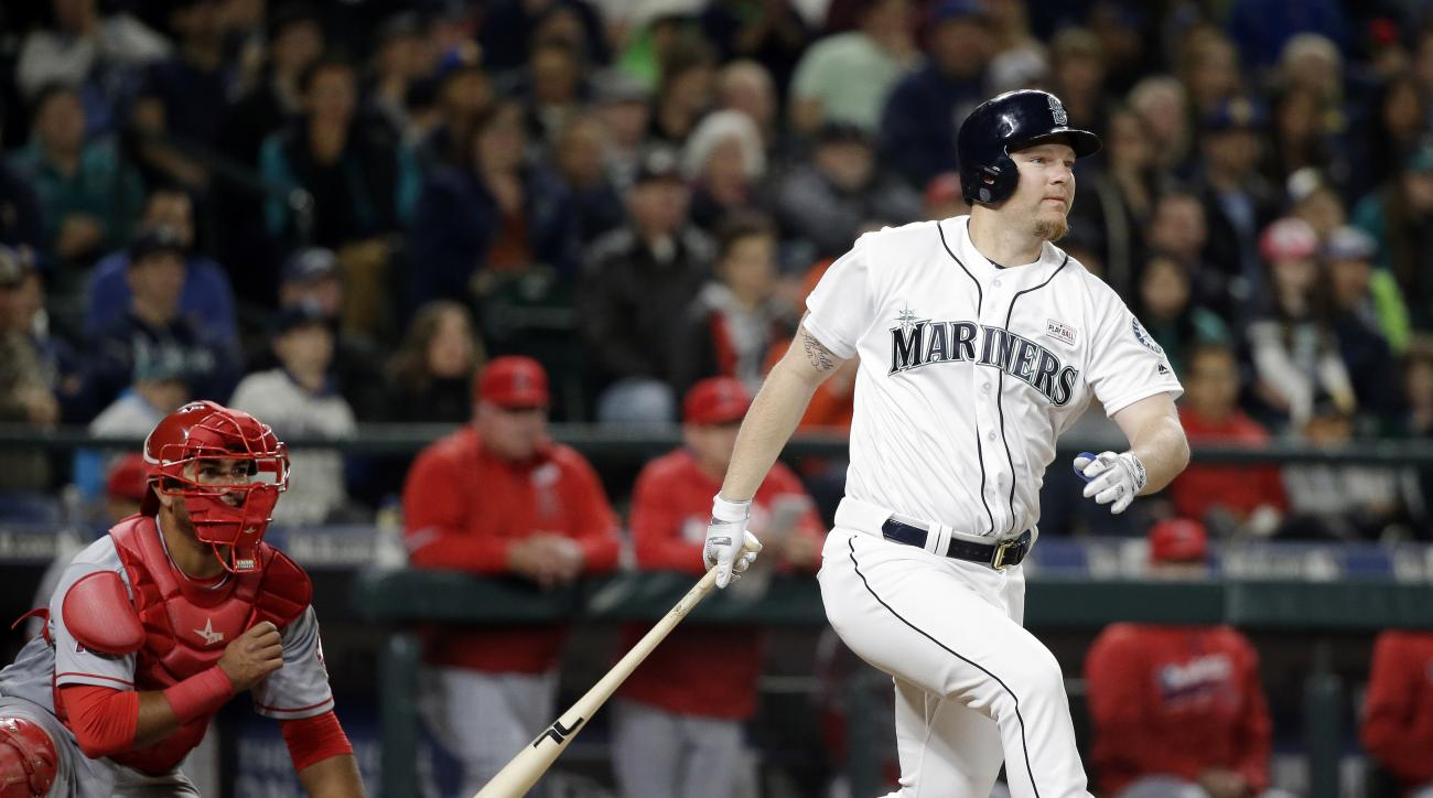 Seattle Mariners' Adam Lind watches his two-run double in front of Los Angeles Angels catcher Carlos Perez during the eighth inning in a baseball game Saturday, May 14, 2016, in Seattle. The Angels won 9-7. (AP Photo/Elaine Thompson)