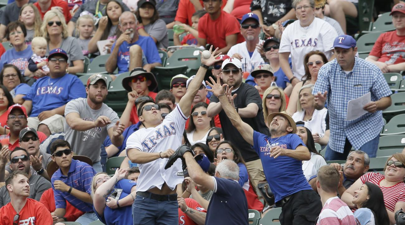 Fans try an catch a foul ball hit into the stands by Toronto Blue Jays' Justin Smoak during the second inning of a baseball game against the Texas Rangers in Arlington, Texas, Sunday, May 15, 2016. (AP Photo/LM Otero)