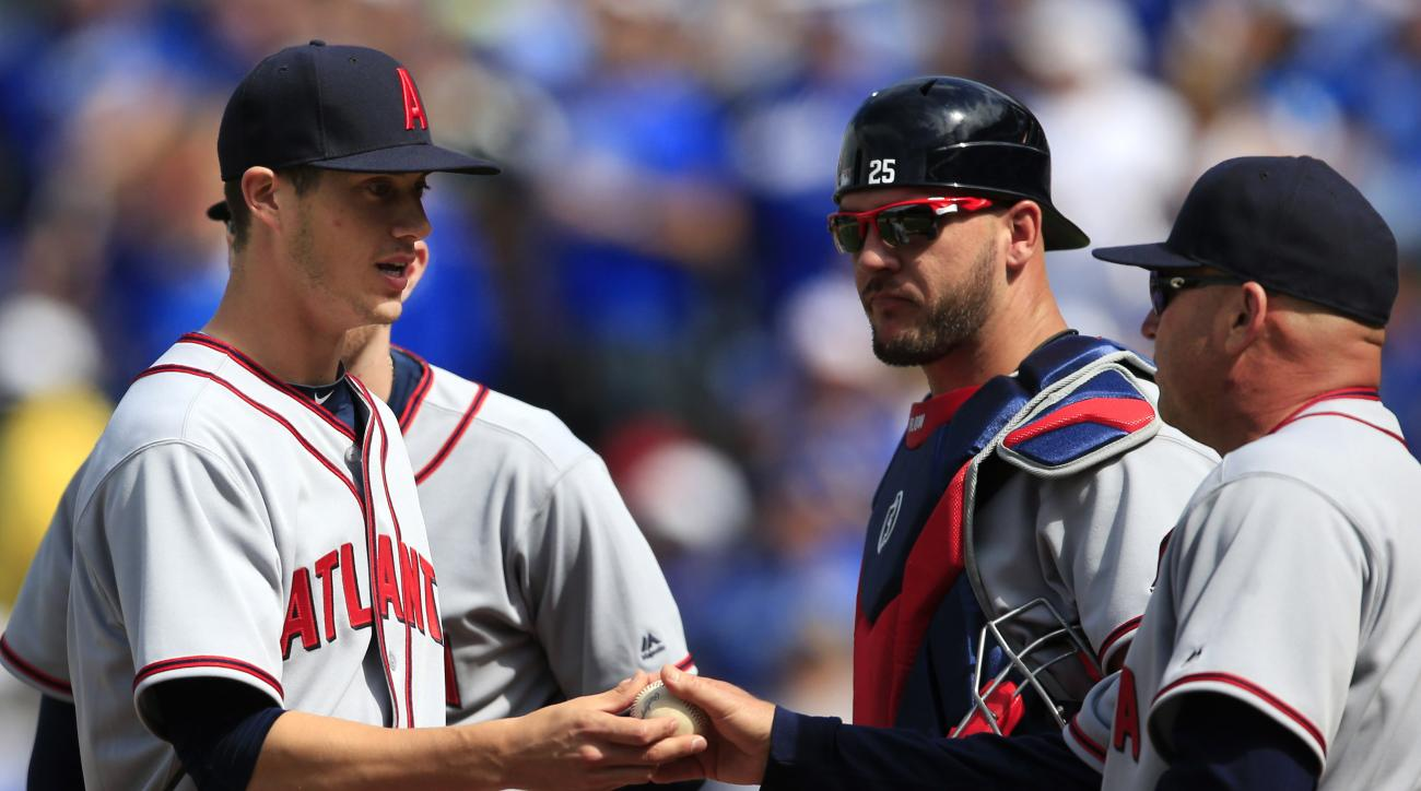 Atlanta Braves starting pitcher Matt Wisler, left, hands the ball to manager Fredi Gonzalez (33) during the eighth inning of a baseball game against the Kansas City Royals at Kauffman Stadium in Kansas City, Mo., Sunday, May 15, 2016. (AP Photo/Orlin Wagn