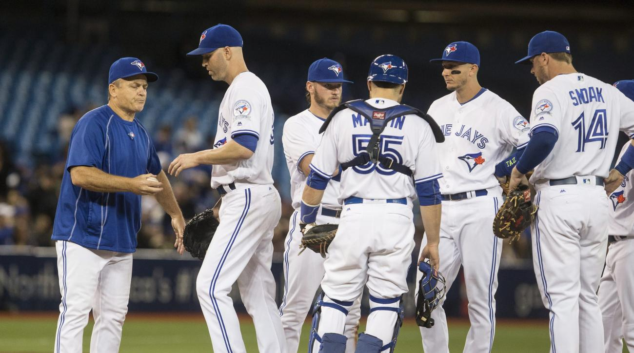 Toronto Blue Jays' starting pitcher J.A. Happ, second left, hands the ball off to Jays' manager John Gibbons, left, as he's pulled during the third inning of a baseball game in Toronto, Monday, May 16, 2016. (Chris Young/The Canadian Press via AP)