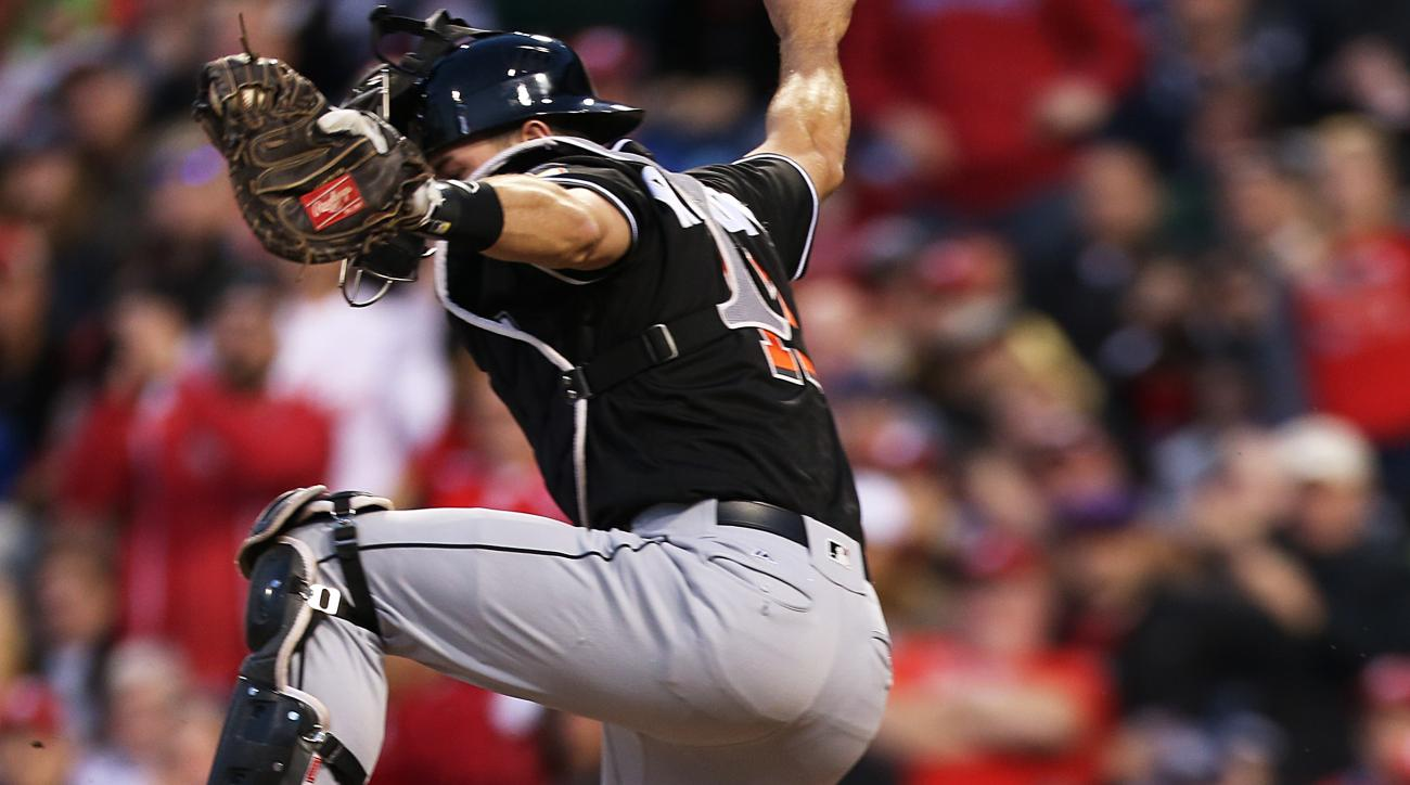 Miami Marlins catcher J.T. Realmuto (11) leaps for the ball as Philadelphia Phillies' Carlos Ruiz (51) scores at home on an RBI by Tyler Goeddel in the fourth inning of a baseball game, Monday, May 16, 2016, in Philadelphia. (AP Photo/Laurence Kesterson)