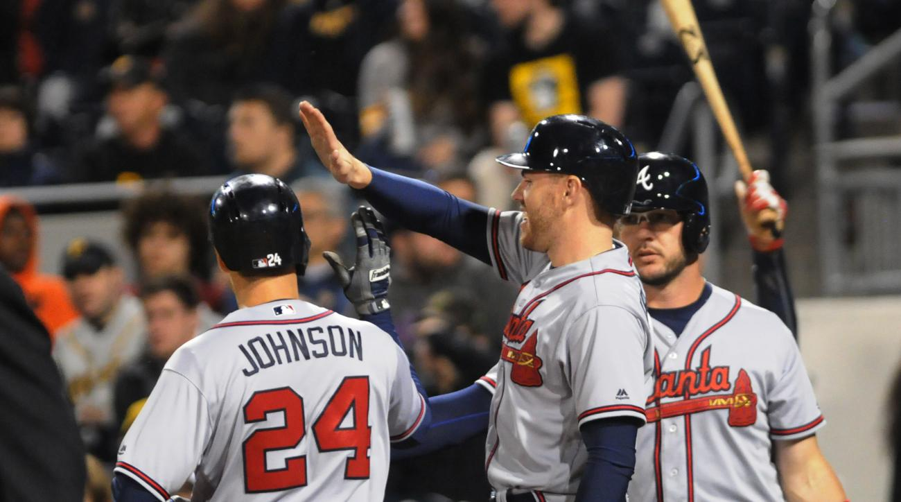 Atlanta Braves' Kelly Johnson, left, is congratulated at the plate after hitting a 3-run home run against the Pittsburgh Pirates in the 8th inning of a baseball game Monday, May 16, 2016 in Pittsburgh. (AP Photo/John Heller)