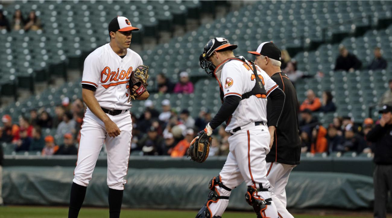 Baltimore Orioles starting pitcher Ubaldo Jimenez stands on the mound as catcher Matt Wieters and coach Scott McGregor approach after walking Seattle Mariners' Kyle Seager in the first inning of a baseball game in Baltimore, Tuesday, May 17, 2016. Seattle