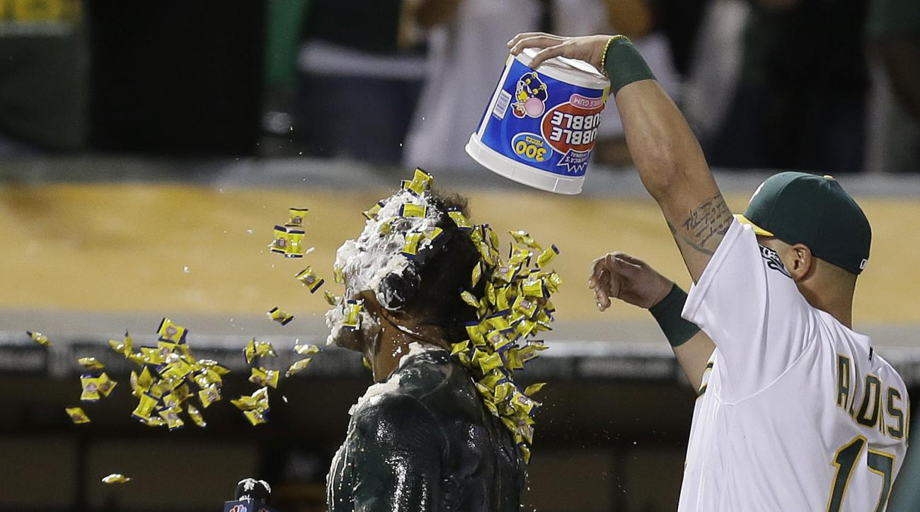 Oakland Athletics' Khris Davis, left, is covered with a pie and bubble gum dumped on him by Yonder Alonso (17) as he speaks during an interview after hitting a walk-off grand slam against the Texas Rangers in a baseball game Tuesday, May 17, 2016, in Oakl