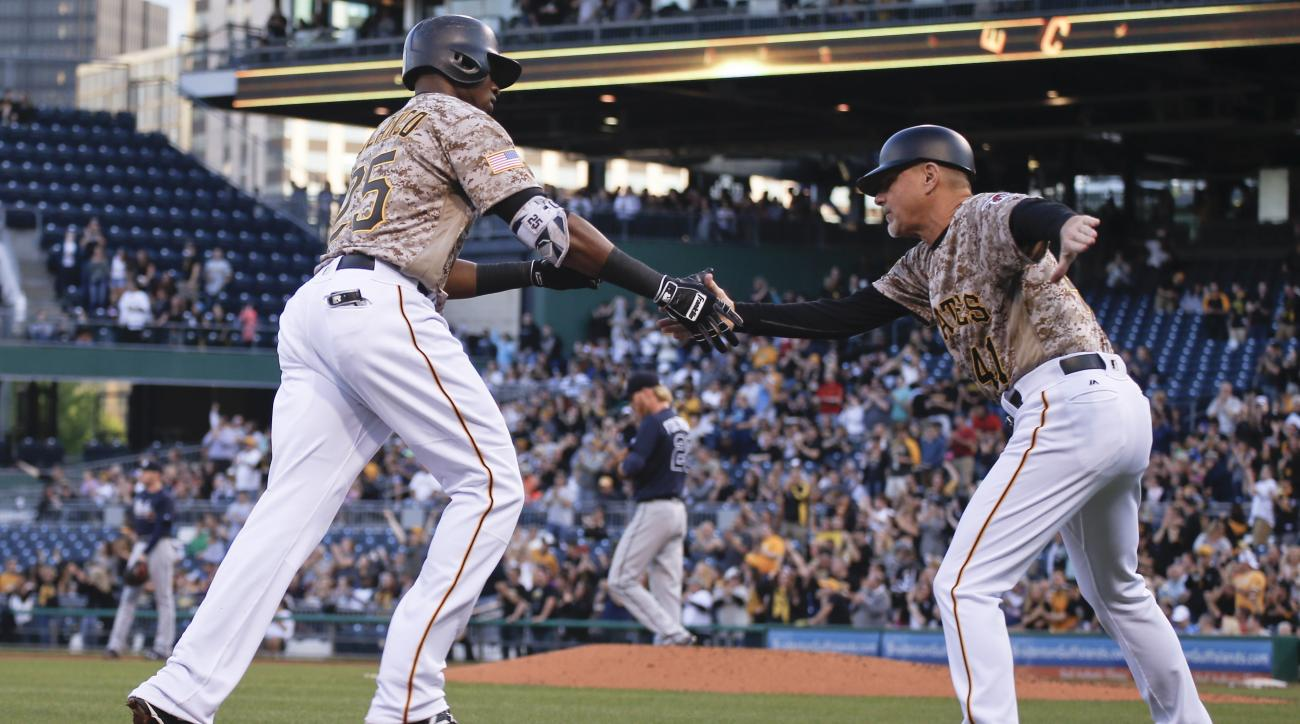 Pittsburgh Pirates' Gregory Polanco,left, is greeted by third base coach Rick Sofield, right, as he rounds the bases after hitting a two-run home run off Atlanta Braves starting pitcher Mike Foltynewicz in the second inning of a baseball game, Thursday, M