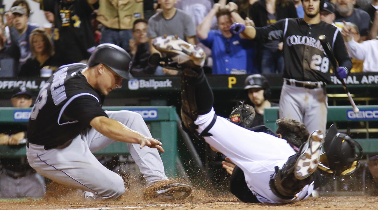 Pittsburgh Pirates catcher Francisco Cervelli, right, falls after tags out Colorado Rockies' Dustin Garneau (13) during the seventh inning of a baseball game Friday, May 20, 2016, in Pittsburgh. (AP Photo/Keith Srakocic)