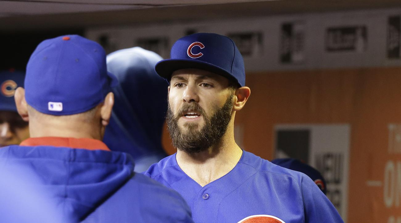 Chicago Cubs starting pitcher Jake Arrieta is greeted in the dugout by pitching coach Chris Bosio, left, after pitching in the seventh inning of the Cubs' baseball game against the San Francisco Giants on Friday, May 20, 2016, in San Francisco. (AP Photo/