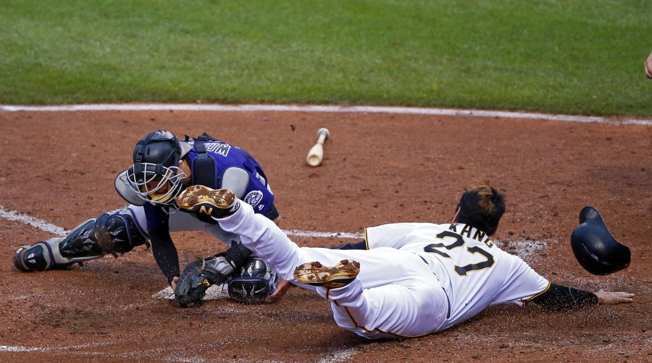 Colorado Rockies catcher Tony Wolters, left, makes the tag on Pittsburgh Pirates' Jung Ho Kang (27) for the out during the fourth inning of a baseball game in Pittsburgh, Saturday, May 21, 2016. Kang was attempting to score from third on a fielder's choic
