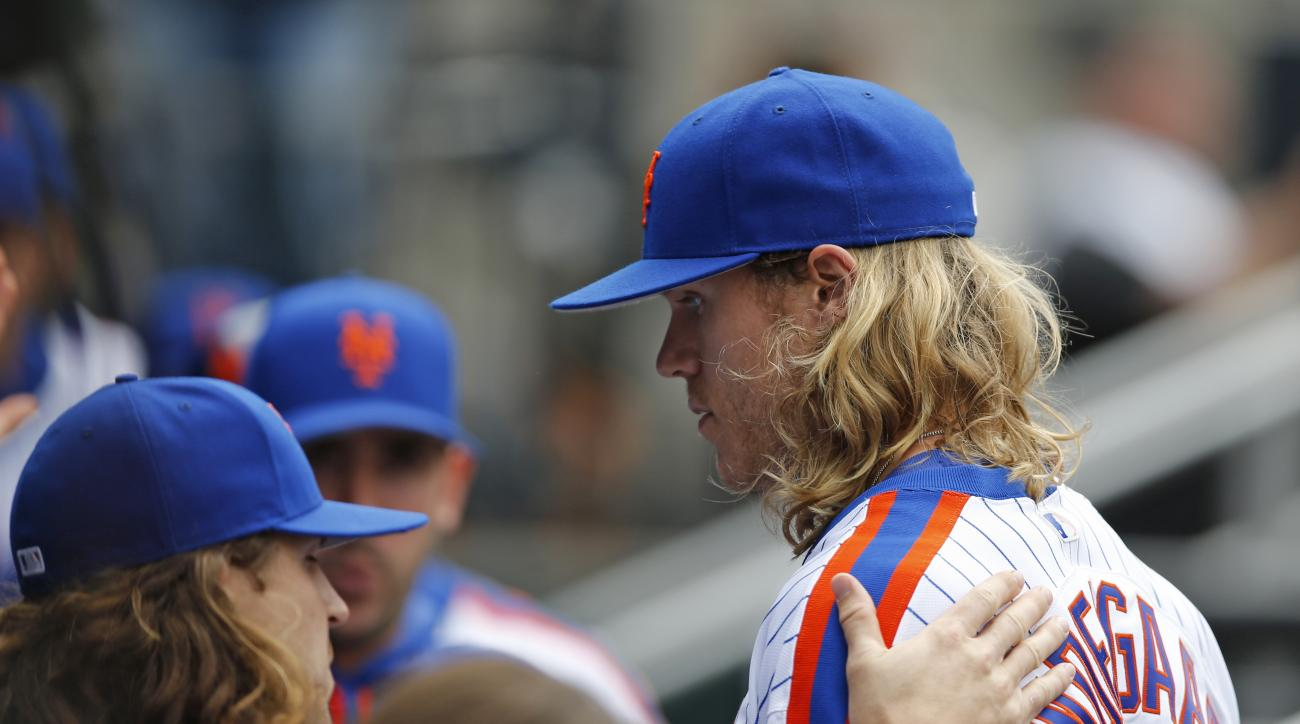 New York Mets starting pitcher Jacob deGrom, left, congratulates Mets' starting pitcher Noah Syndergaard, right, after Syndergaard pitched through seven innings of a baseball game against the Milwaukee Brewers Sunday, May 22, 2016, in New York. (AP Photo/