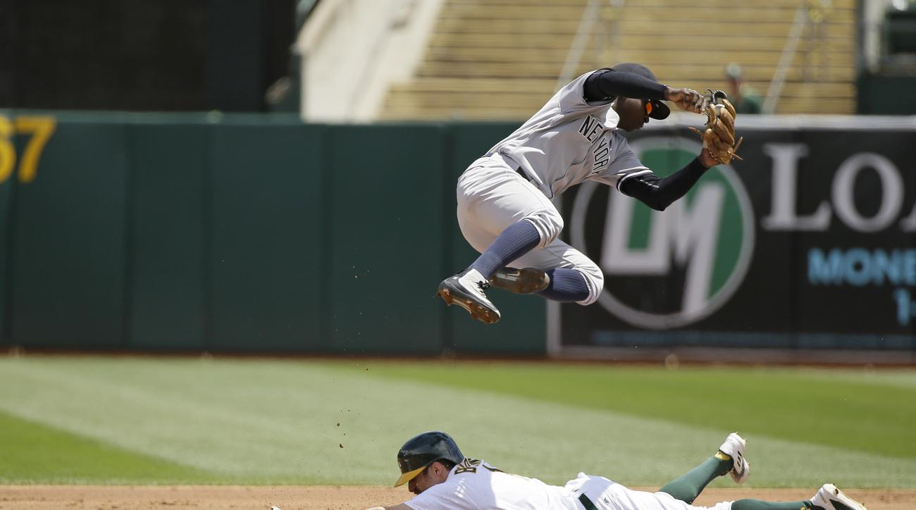 Oakland Athletics' Billy Burns slides safely under New York Yankees shortstop Didi Gregorius to steal second base in the first inning of a baseball game Sunday, May 22, 2016, in Oakland, Calif. (AP Photo/Eric Risberg)