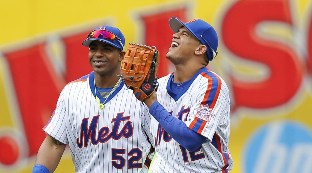 New York Mets outfielders Yoenis Cespedes (52) celebrates the Mets victory with Juan Lagares (12) after a baseball game against the Milwaukee Brewers, Sunday, May 22, 2016, in New York. The Mets defeated the Brewers 3-1. (AP Photo/Kathy Willens)