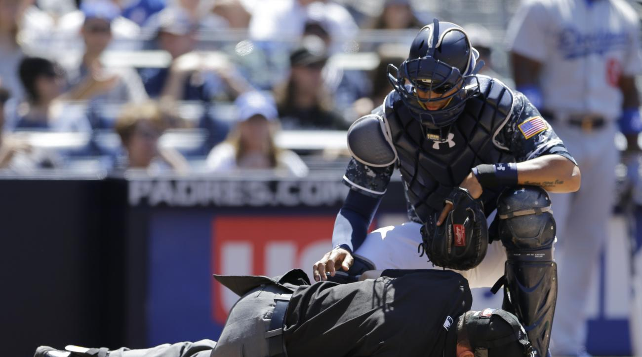 Home plate umpire David Rackley stays down after an injury as San Diego Padres catcher Christian Bethancourt looks on during the fifth inning of a baseball game against the Los Angeles Dodgers, Sunday, May 22, 2016, in San Diego. (AP Photo/Gregory Bull)