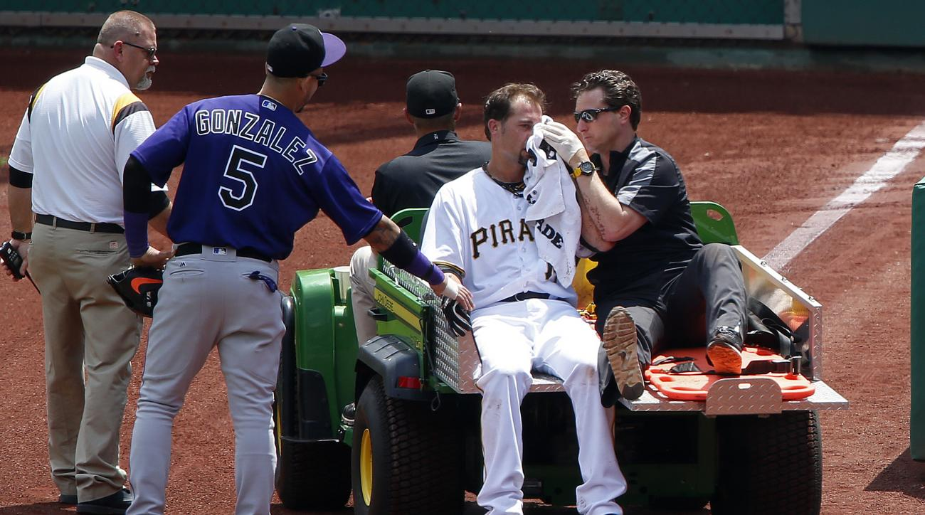 Pittsburgh Pirates pitcher Ryan Vogelsong, center, is carted off the field past Colorado Rockies right fielder Carlos Gonzalez (5) after being hit in the head by a pitch from starting pitcher Jordan Lyles in the second inning of a baseball game in Pittsbu