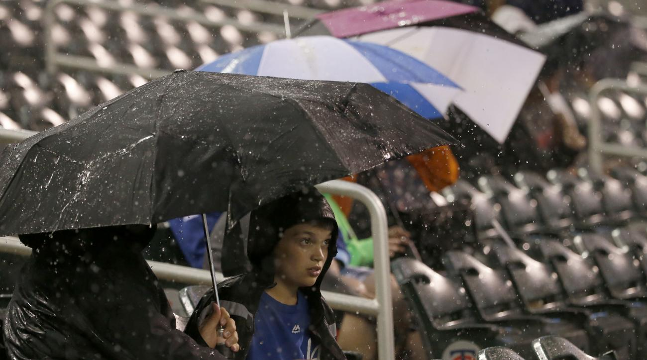A young Kansas City Royals fan takes cover under an umbrella as a rain delay is called during the third inning of a baseball game between the Royals and the Minnesota Twins in Minneapolis, Monday, May 23, 2016. (AP Photo/Ann Heisenfelt)