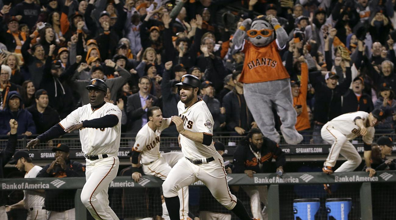 Fans cheer and San Francisco Giants players run out of the dugout as Brandon Belt, center, rounds third base to score the winning run during the ninth inning of a baseball game against the San Diego Padres in San Francisco, Monday, May 23, 2016. The Giant