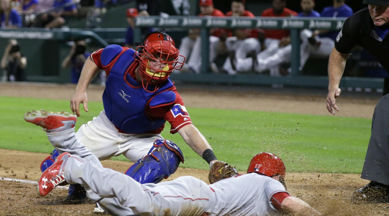 Los Angeles Angels' Shane Robinson, bottom, is tagged out at home by Texas Rangers catcher Bryan Holaday during the sixth inning of a baseball game in Arlington, Texas, Tuesday, May 24, 2016. (AP Photo/LM Otero)
