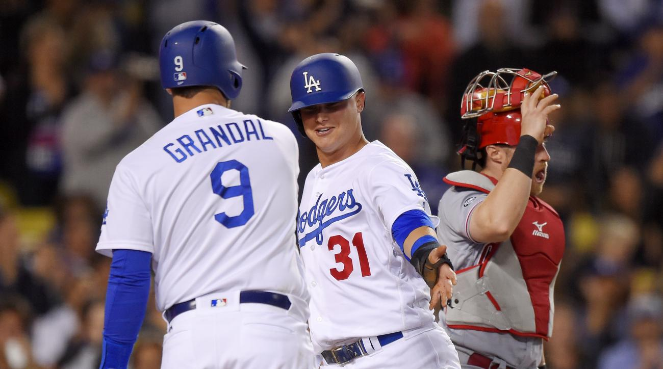 Los Angeles Dodgers' Joc Pederson, center, is congratulated by Yasmani Grandal, left, after scoring on a throwing error by Cincinnati Reds catcher Tucker Barnhart, right, during the fourth inning of a baseball game, Tuesday, May 24, 2016, in Los Angeles.