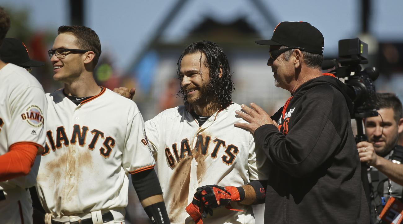 San Francisco Giants manager Bruce Bochy, right, greets Brandon Crawford, center, at the end of their baseball game against the San Diego Padres on Wednesday, May 25, 2016, in San Francisco. San Francisco won the game 4-3 in 10 innings. At left is the Gia
