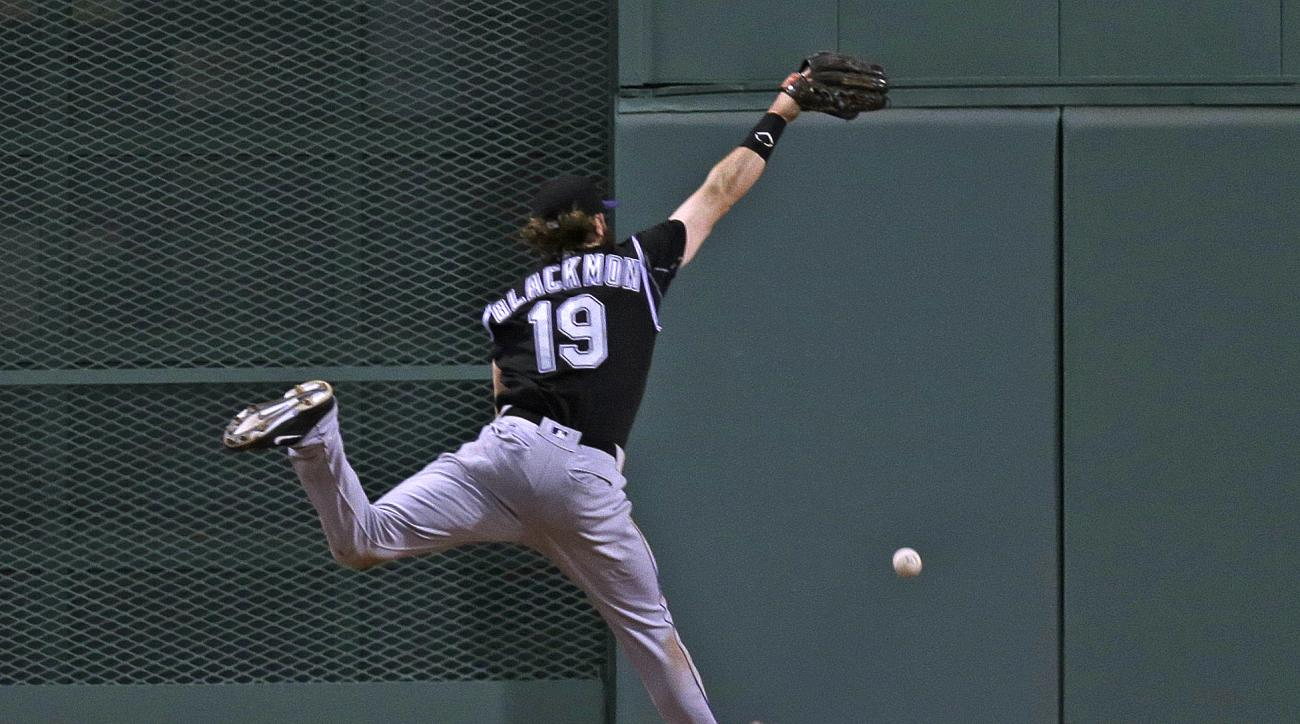 Colorado Rockies center fielder Charlie Blackmon leaps but can't make the play on a two-run triple by Boston Red Sox's Blake Swihart during the fourth inning of a baseball game against the Colorado Rockies in Boston, Wednesday, May 25, 2016. (AP Photo/Cha