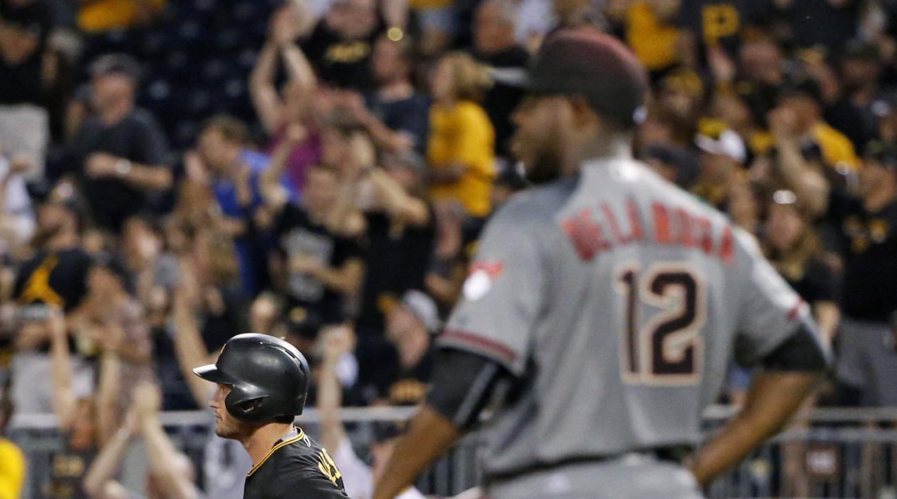 Pittsburgh Pirates' David Freese, left, rounds first behind Arizona Diamondbacks starting pitcher Rubby De La Rosa (12) after hitting a two-run home run during the fifth inning of a baseball game in Pittsburgh, Wednesday, May 25, 2016. (AP Photo/Gene J. P