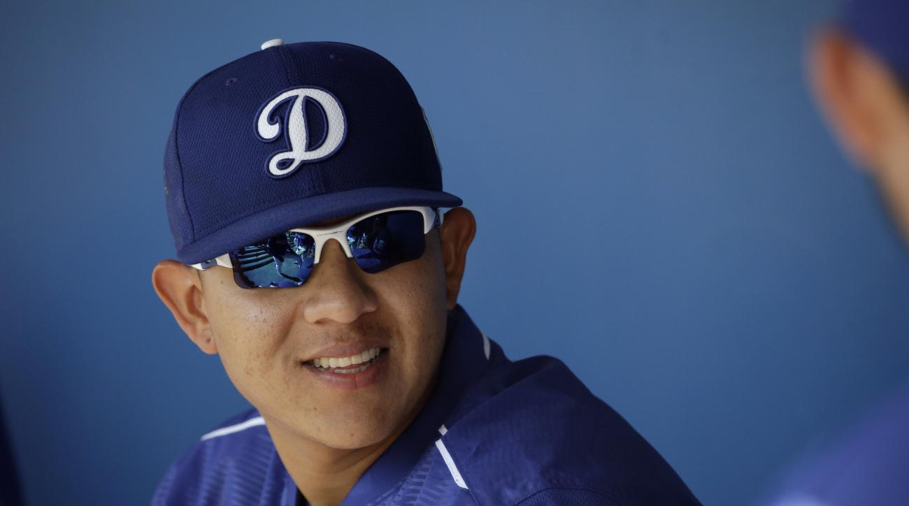 FILE - In this March 14, 2016, Los Angeles Dodgers pitcher Julio Urias smiles while talking to teammates in the dugout during a spring training baseball game against the Milwaukee Urias, 19, is set to make his highly anticipated major league debut for the