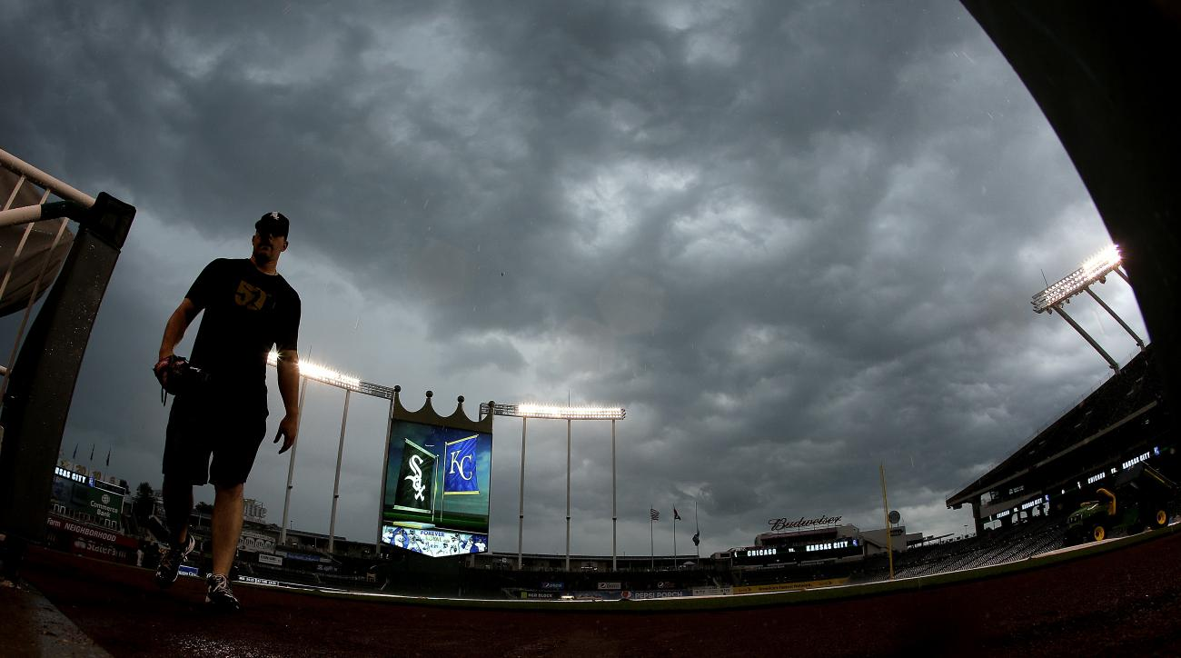 A player for the Chicago White Sox heads for the dugout as a thunderstorm moves over Kauffman Stadium before a baseball game against the Kansas City Royals on Thursday, May 26, 2016, in Kansas City, Mo. The game was postponed due to rain. (AP Photo/Charli