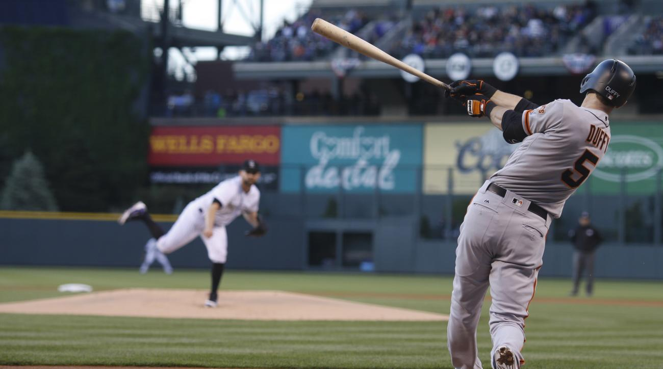 San Francisco Giants' Matt Duffy, front, flies out on a pitch from Colorado Rockies starting pitcher Tyler Chatwood to end the top of the first inning of a baseball game Friday, May 27, 2016, in Denver. (AP Photo/David Zalubowski)
