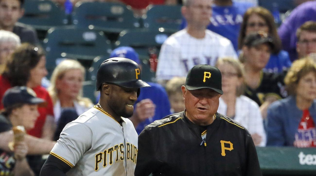 Pittsburgh Pirates' Starling Marte hops on one foot as manager Clint Hurdle watches after Marte was hit by a pitch from Texas Rangers starter Cole Hamels during the fifth inning of a baseball game, Friday, May 27, 2016, in Arlington, Texas. Marte remained